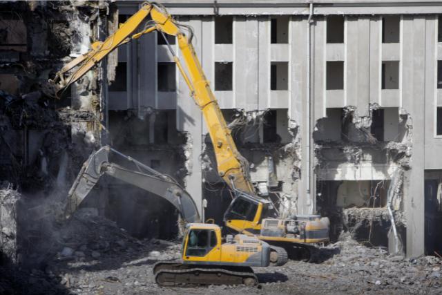 Building Demolition with 2 big yellow cranes
